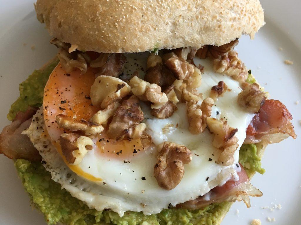 broodje met avocado, gepocheerd ei, uitgebakken spek en geroosterde walnoten